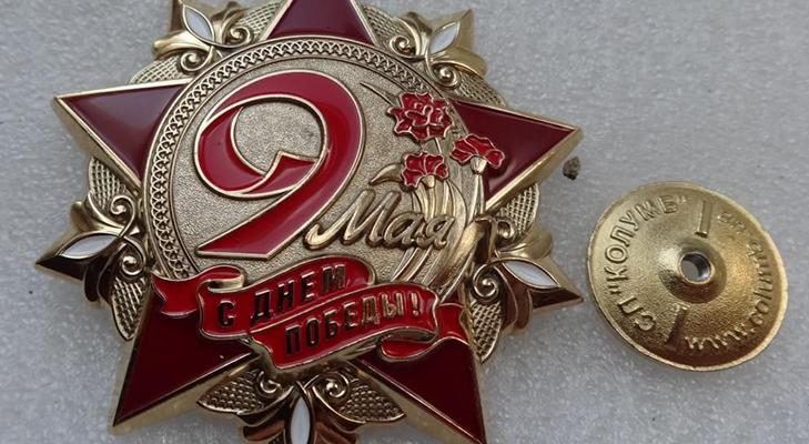 Красная гвоздика на значках к Дню победы